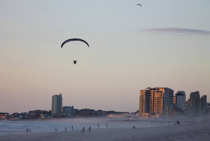 A powered paraglider flies over Table View beach